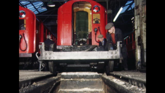 Sequence showing mechanics repairing and painting carriages from Glasgow's underground railway service