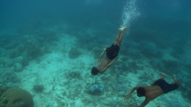 Sequence showing Moken men freediving to the ocean floor to search for food.