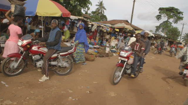 Sequence showing motorcycles on a busy street running through a Sierra Leonean market.