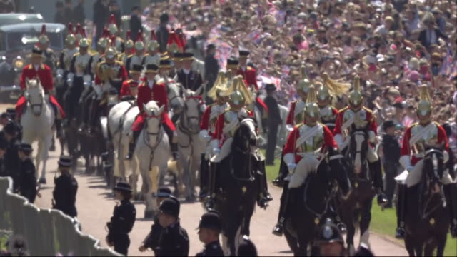 Sequence showing mounted cavalry escorting the newlywed Duke and Duchess of Sussex down Windsor Great Park's Long Walk
