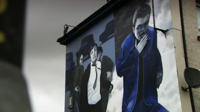 Sequence showing murals of the People's Gallery depicting a British soldier with a sledgehammer and Bloody Sunday in the Bogside, Londonderry/Derry, Northern Ireland.