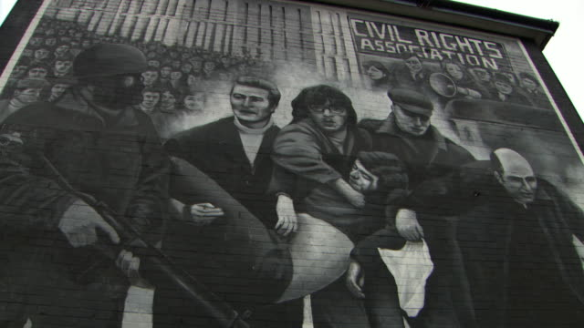 Sequence showing murals of the People's Gallery (by the Bogside Artists) in the Bogside area of Londonderry/Derry depicting the death of Jackie Duddy on Bloody Sunday and the MP Bernadette McAliskey (née Devlin) with megaphone, Northern Ireland.