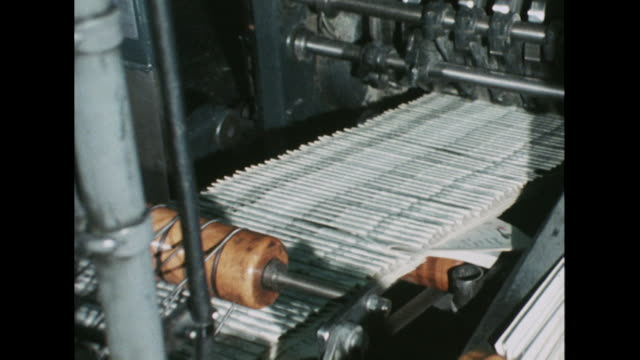 Sequence showing newspapers moving along a conveyor belt at a printers