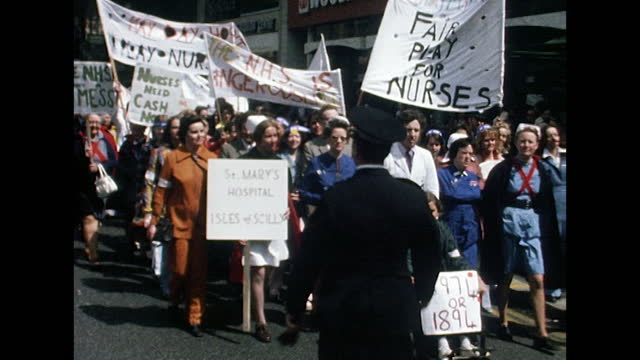 sequence showing nhs nurses and doctors in uniform marching for fair pay on the streets of london; 1974. marchers on city street with signs. nurses... - waist up stock videos & royalty-free footage