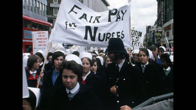 sequence showing nhs nurses marching for fair pay on the streets of london; 1974. nurses in uniform holding placards march past the camera. women's... - hat stock videos & royalty-free footage