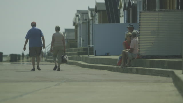 sequence showing older people chatting and walking outside beach huts at the seaside in walton-on-the-naze in essex, uk. - couple relationship stock videos & royalty-free footage