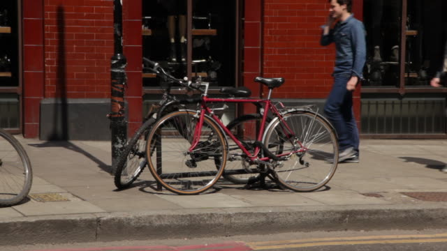 sequence showing parked bikes chained to stands on an east london street, uk. - lock stock videos & royalty-free footage