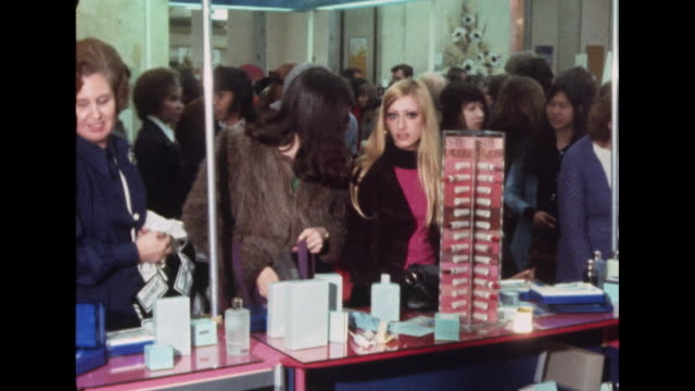 Sequence showing people browsing goods on a department store's beauty counter
