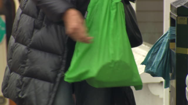 sequence showing people carrying a green, reusable shopping bag and a red shoulder bag, stratford-upon-avon, uk. - bärkasse bildbanksvideor och videomaterial från bakom kulisserna