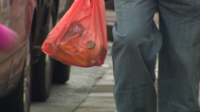 sequence showing people carrying plastic carrier bags from sainsbury's, clinton's and poundland in stratford-upon-avon, uk. - shopping bag stock videos & royalty-free footage