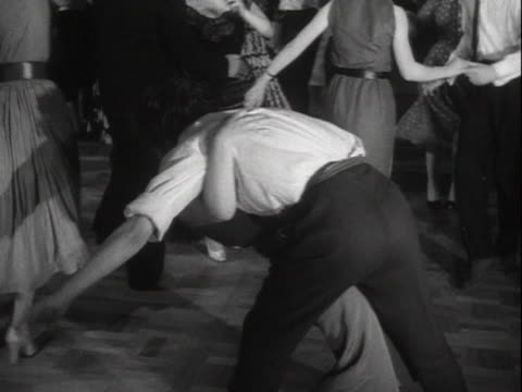 vidéos et rushes de sequence showing people dancing to rock and roll music in a dance hall. - rock