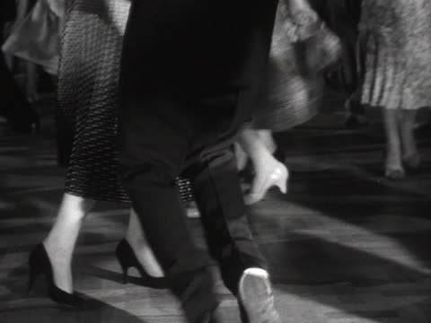 stockvideo's en b-roll-footage met sequence showing people dancing to rock and roll music in a dance hall - 1956
