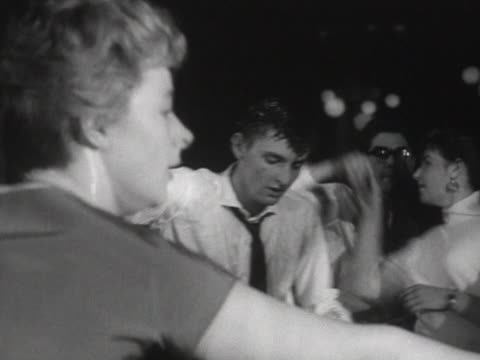 sequence showing people dancing to rock and roll music in a dance hall - klassischer rock and roll stock-videos und b-roll-filmmaterial