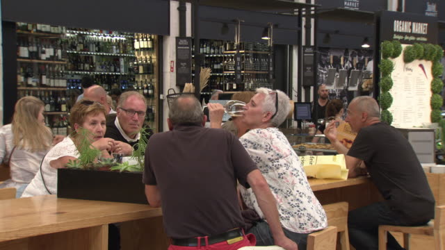 Sequence showing people sharing food and drink at Lisbon's Time Out Market in the Mercado da Ribeira in Cais do Sodré Portugal FKIY886P ABRA690X