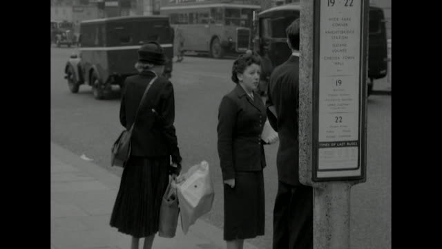 sequence showing people waiting at a bus stop in central london. - doppeldeckerbus stock-videos und b-roll-filmmaterial