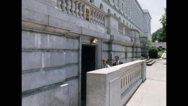 vidéos et rushes de sequence showing people walking into nuclear fallout shelters in washington d.c. beneath government buildings during the cold war era; 1974. - retombée radioactive