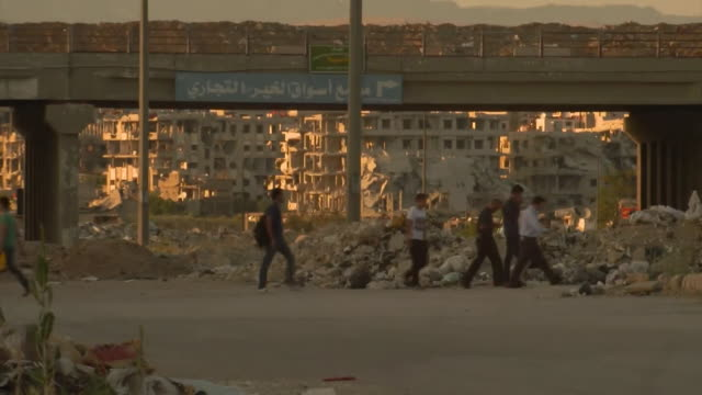 Sequence showing people walking past rubble and severely damaged buildings in Damascus due to the ongoing Syrian civil war
