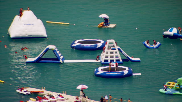 Sequence showing people who have disembarked from a large cruise ship enjoying inflatable, floating slides and trampolines at Paradise Cove, northern Haiti.