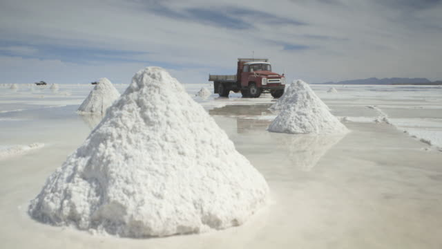 sequence showing piles of salt standing in brine on bolivia's salt flats. - salt mineral stock videos and b-roll footage
