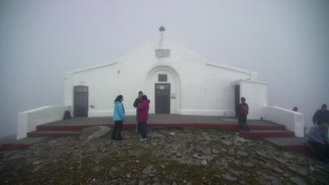 sequence showing pilgrims atop croagh patrick reaching the chapel teampall phadraig on reek sunday, county mayo, republic of ireland. - pilgrimage stock videos & royalty-free footage