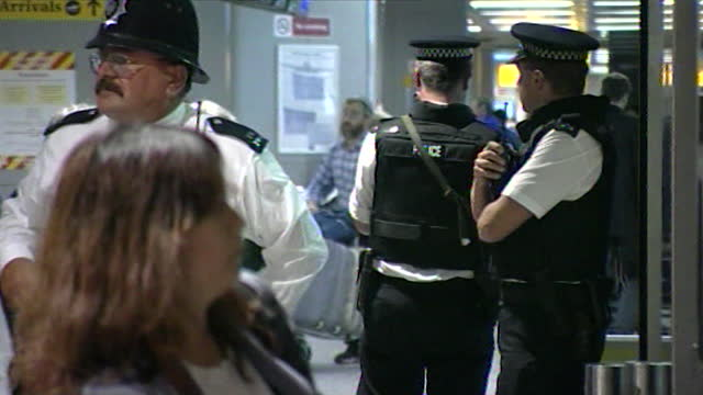 sequence showing police officers on patrol inside heathrow airport's check-in area the day after the 9/11 attacks; 2001. - examining stock videos & royalty-free footage