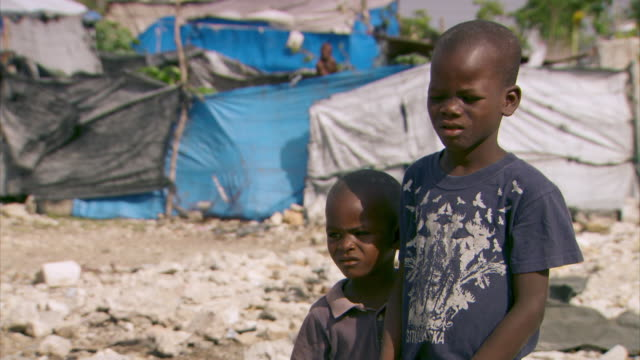 Sequence showing poverty-stricken Port-au-Prince families living in makeshift shelters approximately four years after Haiti's 2010 earthquake.