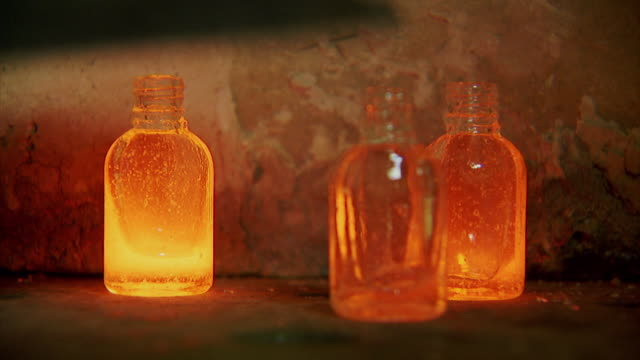 Sequence showing processes involved with producing recycled glass bottles at a glass recycling foundry in Dhaka, Bangladesh.