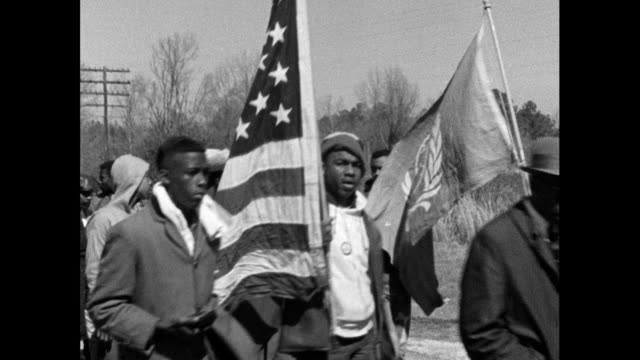 vídeos de stock, filmes e b-roll de sequence showing protest marchers walking down the highway on route from selma to montgomery; 22nd march 1965. marchers walking past camera carrying... - 1965