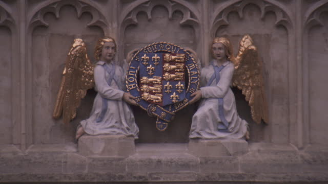 Sequence showing reliefs of a crest, Mary Magdalene and angels on the grounds of Eton College, UK.