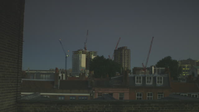 sequence showing rooftops and cranes in east london at dusk, uk. - east london stock videos and b-roll footage