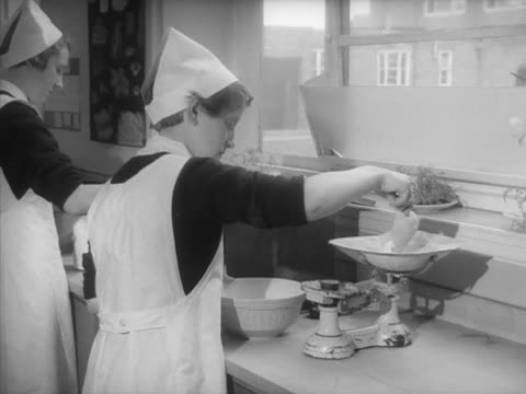 sequence showing school girls measuring out ingredients during a cookery lesson - home economics stock videos & royalty-free footage