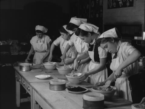 stockvideo's en b-roll-footage met a sequence showing school girls mixing cake mix during a cookery class - huishuidkunde