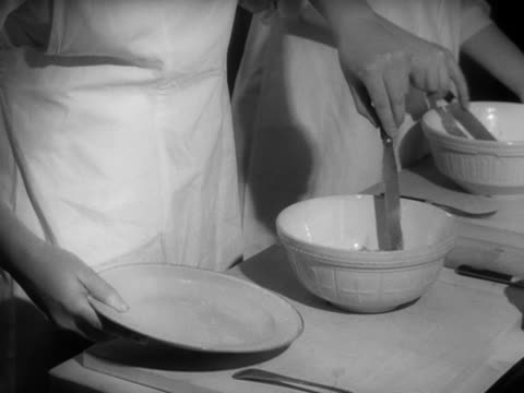 stockvideo's en b-roll-footage met sequence showing school girls mixing ingredients to make hot cross buns during a cookery lesson. - home economics
