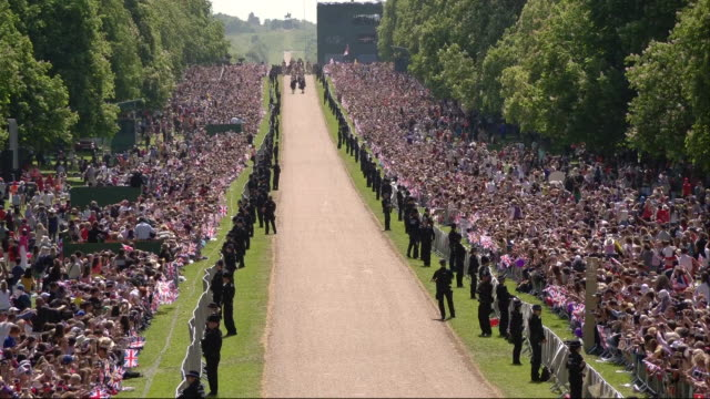 Sequence showing scores of wellwishers cheering the newlywed Duke and Duchess of Sussex as they travel along the Long Walk in Windsor Great Park