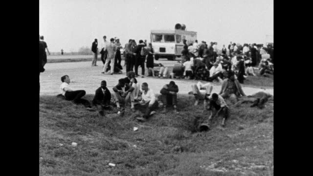 stockvideo's en b-roll-footage met sequence showing selma marchers stopping to rest on the roadside on the way to montgomery; 24th march 1965. pan right across a large group of... - 1965