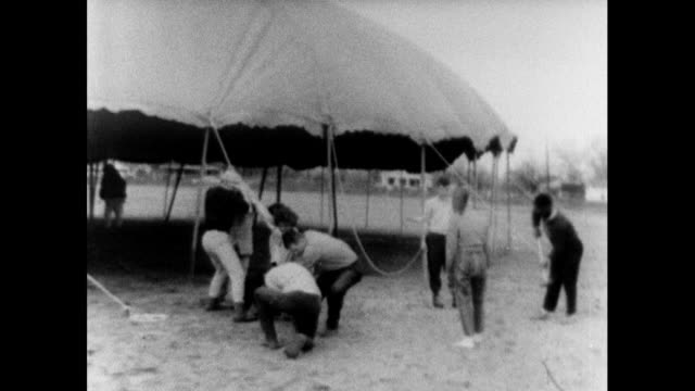 vídeos de stock, filmes e b-roll de sequence showing selma to montgomery marchers working together to set up a large tent in a campsite on the way to montgomery, possibly in st jude,... - 1965