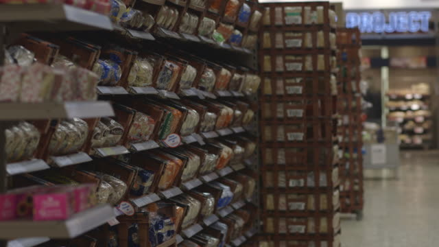 sequence showing shelves displaying loaves of bread in a uk supermarket aisle. - 店頭点の映像素材/bロール