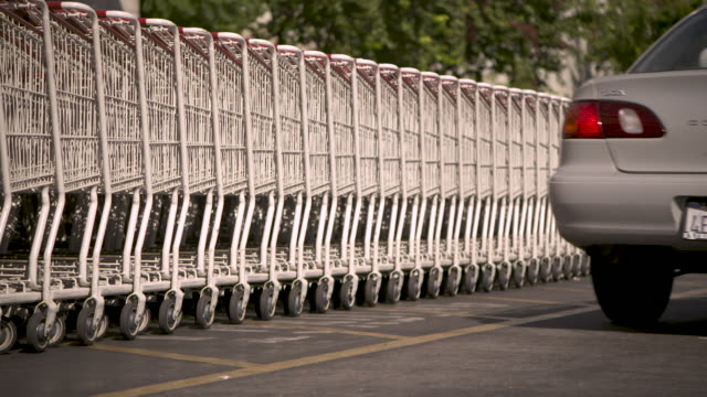 sequence showing shopping trolleys stacked in the car park of a costco, usa. - tidy stock videos & royalty-free footage
