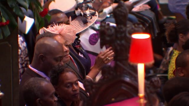 sequence showing shots of the congregation at the windrush commemoration in westminster abbey - religious service stock videos and b-roll footage