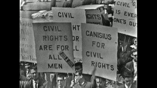 stockvideo's en b-roll-footage met sequence showing signs being carried by large crowds of protestors as the civil rights march leaves selma, alabama; 21st march 1965. - 1965