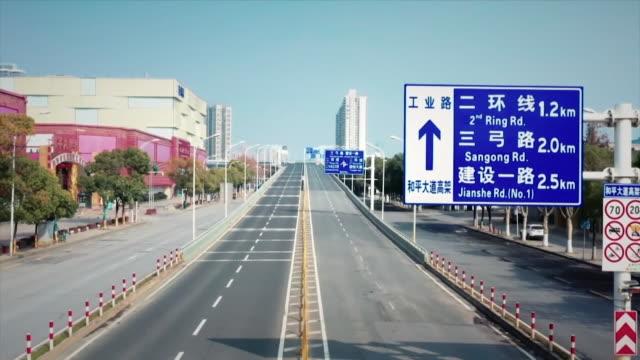 vidéos et rushes de sequence showing skyline of beijing followed by empty deserted roads due to the coronavirus - pékin