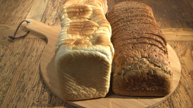 sequence showing sliced white and seeded brown bread on a breadboard on a wooden table. - bread stock videos & royalty-free footage