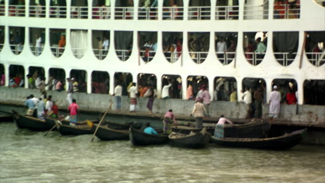 Sequence showing small commuter rowing boats jostling for space amongst larger vessels such as ferries in the bustling port of Dhaka Sadarghat on the Buriganga River, Dhaka, Bangladesh.
