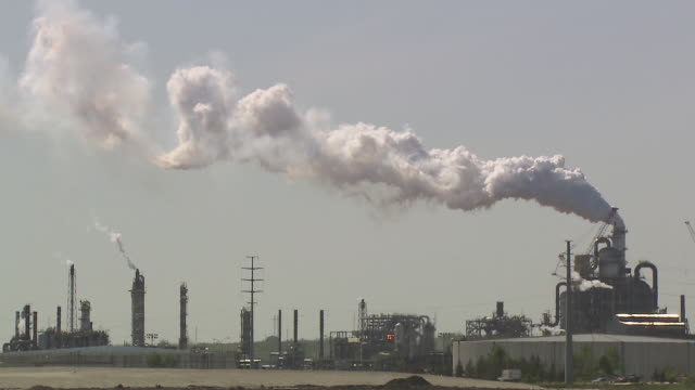vídeos de stock, filmes e b-roll de sequence showing smoke billowing out of chimneys at the athabasca oil sands refinery in alberta, canada.  - combustível fóssil