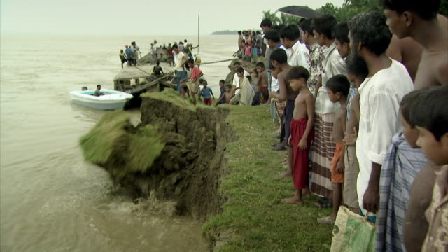 sequence showing soil breaking away as part of dramatic erosion on the banks of the river padma (known as the ganges in india) in bangladesh. - sandbag stock videos and b-roll footage