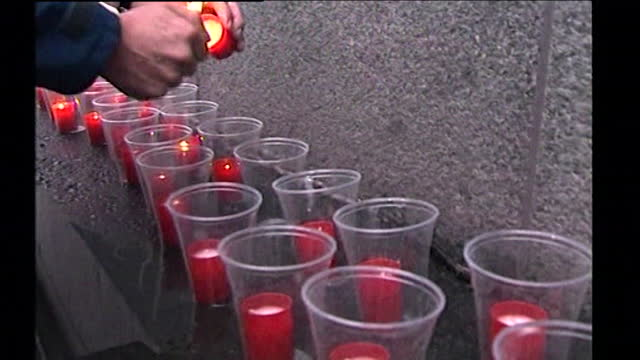 sequence showing someone lighting red votive candles outside the us embassy in london on september 11th 2001. - flame stock videos & royalty-free footage