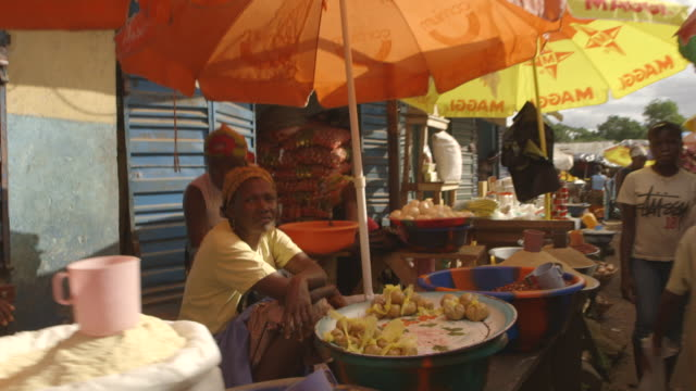 POV sequence showing stallholders at a busy Sierra Leonean market.
