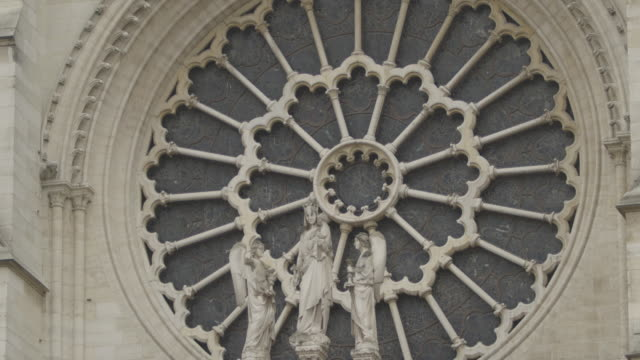 Sequence showing statues depicting the Virgin Mary holding Jesus Christ with angels in front of the rose window on the West facade of Notre Dame de Paris, France.