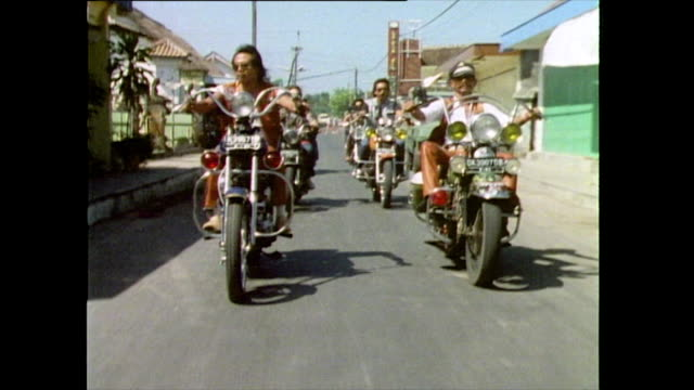 vídeos de stock e filmes b-roll de sequence showing the bali chapter of the hell's angels leaving a petrol station and driving through the streets; 1985. - 1985