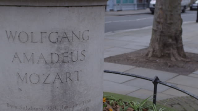 sequence showing the base of the wolfgang amadeus mozart statue in orange square in belgravia in london. - engraved image stock videos and b-roll footage